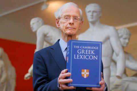 Professor James Diggle holding the Cambridge Greek Lexicon